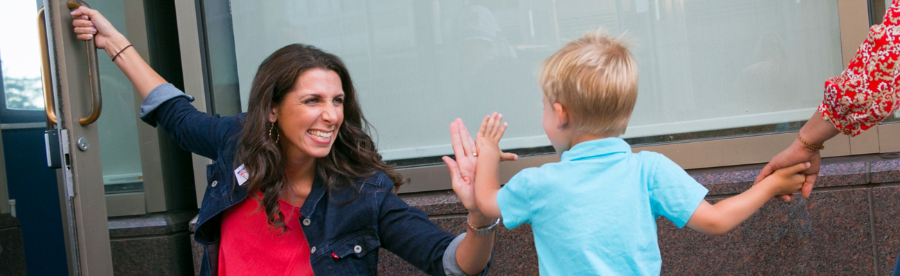 teacher giving young boy high five