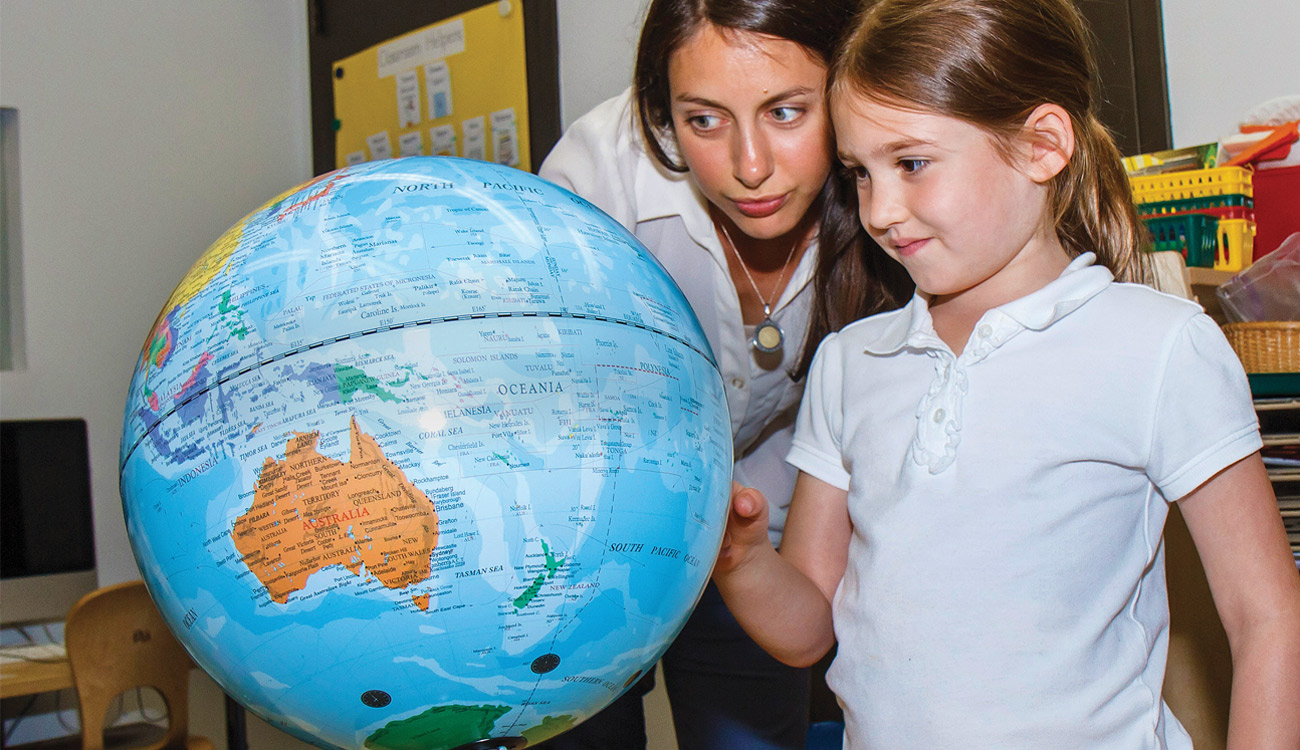 teach and student looking at globe